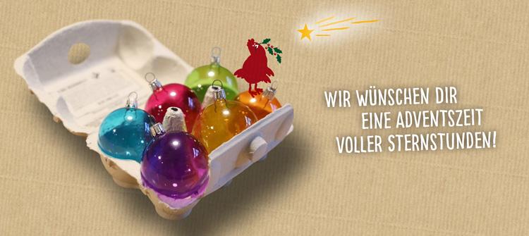 """Das Bild zeigt eine Eierschachtel mit bunten Baumkugeln und dem Hühnchen von Dein-Land-Ei.de mit einem Stechpalmenzweig im Schnabel. Der Text lautet: """"Wir wünschen Dir eine Adventszeit voller Sternstunden!"""""""